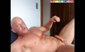 Mature muscled guy stroking and shooting his load