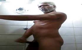 Mature black guy with curly hair masturbates in the gym shower
