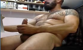 Muscle bearded guy stroking his cock while playing with his computer