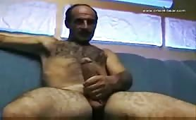 Mature european hairy guy stroking his cock in front of a webcam