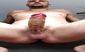 Bald dude stroking his huge cock in front of a webcam