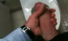Stroking my thick cock in a public toilet