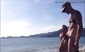 Drunk man jerking his huge cock on the beach in front other guys